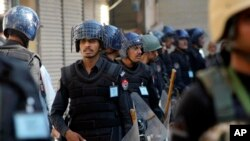 Pakistani police guard a Shi'ite procession during Muharram in Peshawar, Pakistan, Oct. 22, 2015.