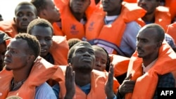 "Kaum migran dan pengungsi duduk di perahuk karet menunggu diselamatkan oleh Topaz Responder, sebuah perahu penyelamat yang dioperasikan LSM Malta ""Moas"" dan Palang Merah Italia, pada tanggal 4 November 2016 (foto: AFP Photo/Andreas Solaro)"