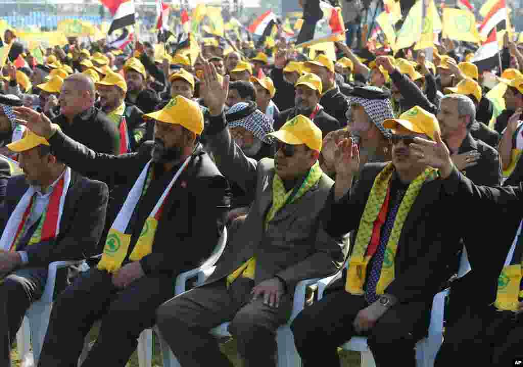 Para pendukung partai Syiah terbesar di Irak, Dewan Tertinggi Islami Irak, mendengarkan pemimpin mereka Ammar al-Hakim dalam sebuah pawai yang menandai perayaan Ashura di Baghdad (13/11). (AP/Karim Kadim)