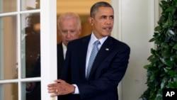 El presidente Barack Obama sale de su despacho en la Casa Blanca seguido del vicepresidente Biden, para hablar del tema migratorio.