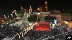 Peziarah dan wisatawan merayakan Natal di Alun-Alun Manger, di luar Gereja Nativity, Bethlehem di Tepi Barat. (AP/Adel Hana)