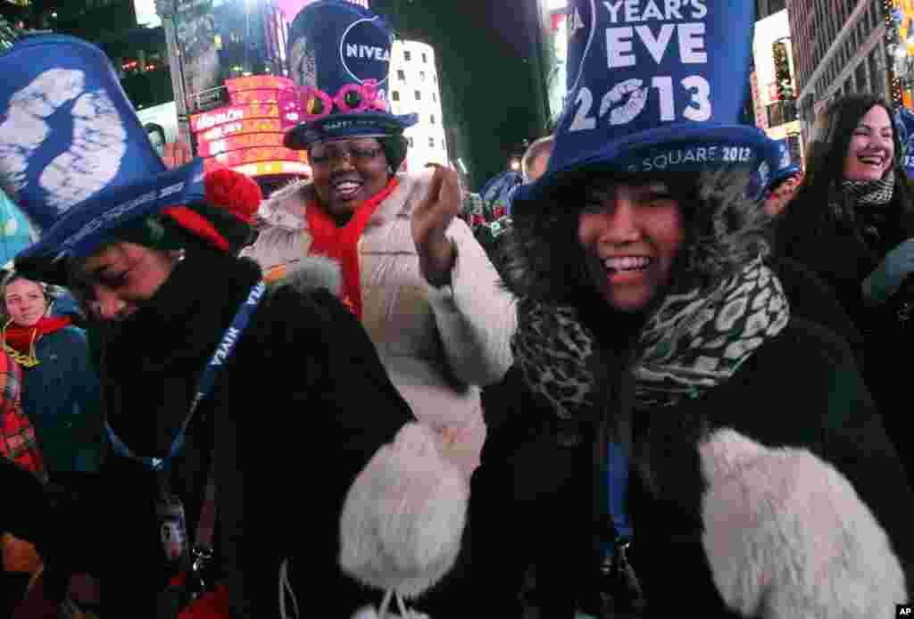Tatiana Rakotovazaha, from Madagascar, foreground left, Aurielle Williams, from Kansas, center, and Yayoi Okayama, from Japan, foreground right, dance as they take part in the New Year's Eve festivities in New York's Times Square on Dec. 31, 2012.