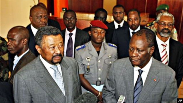 Ivory Coast's internationally-recognized President, Alassane Ouattara, right, stands with African Union Commission Chairman, Jean Ping, left, addressing journalists in Abidjan, March 5, 2011