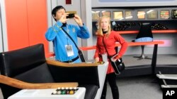Keith Schubert (L) of Peru, New York, dressed as Star Trek's Mr. Spock, and his daughter Tiffany, dressed as a crew member, take photographs during a tour of a replica starship Enterprise, in Ticonderoga, New York, Aug. 13, 2016.