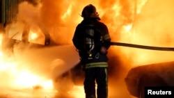 Par petugas pemadam kebakaran memadamkan api dari sebuah mobil yang terbakar pada malam Tahun Baru di Lille, 31 Desember 2013. (Foto:Dok)