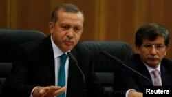 Turkish Prime Minister Tayyip Erdogan addresses the media next to Foreign Minister Ahmet Davutoglu (R) at Esenboga Airport in Ankara, Nov. 21, 2013.