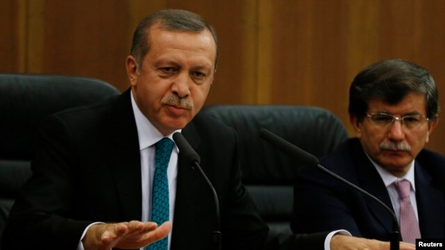 Turkish Prime Minister Tayyip Erdogan addresses the media next to Foreign Minister Ahmet Davutoglu (R) at Esenboga Airport in Ankara, Nov. 21, 2013.