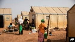 FILE - Displaced women prepare food at Kaya Camp, some 100 kms north of Ouagadougou, Burkina Faso, Feb. 8, 2021. The country's government is at loggerheads with a media outlet over claims displaced women have been forced into sex for food aid.