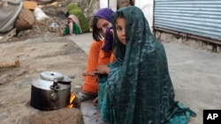 FILE - Internally displaced girls warm up by a stove after their family left their village in the Achin district of Afghanistan, due to clashes between the Islamic State group and other insurgent groups.