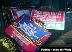 Karangan bunga di dekat pintu masuk bagian belakang kompleks DPR di Senayan dari berbagai organisasi perempuan sebagai bentuk keprihatinan dan mendesak DPR agar segera mengesahkan Rancangan Undang-Undang Penghapusan Kekerasan Seksual (RUU PKS), Jakarta,