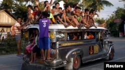 "FILE - Residents ride on top of an overcrowded ""jeepney"", a locally manufactured public transport, along a highway in Mogpog town on Marinduque island in central Philippines, April 8, 2015."