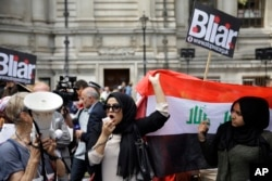 A British Iraqi protester holds up an Iraqi flag, during a protest, outside the Queen Elizabeth II Conference Centre in London, after the publication of the Chilcot report into the Iraq war, July 6, 2016.
