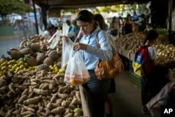 Carmen Victoria Gimenez, 43, shops at a farmers market in the middle-class district of Los Dos Caminos, in Caracas, Venezuela, Feb. 14, 2019.