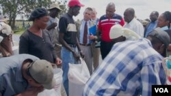 FILE PHOTO: U.S. ambassador to Zimbabwe, Bruce Wharton (in jacket and tie), talking to villagers receiving World Food Program (WFP) food aid in Umguza, a rural area in Matabeleland North province, about 400 kilometers southwest of Harare.