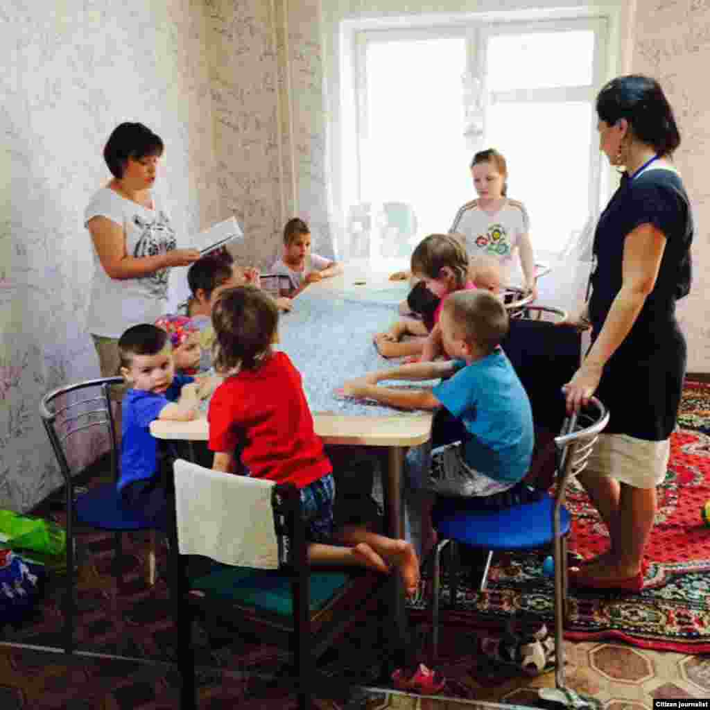 Volunteer psychologists read to internally displaced children (referred to as IDP) at a resettlement house in Kyiv, June 3, 2015. (Daniel Schearf/VOA)