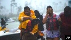 Une famille escortée dans une zone sûre après avoir été secourue aux Bahamas, le mardi 3 septembre 2019. (AP Photo / Ramon Espinosa)