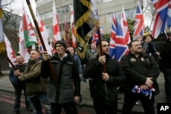 FILE - Members of Britain First, a far-right nationalist political party, protest across the street from London Central Mosque during prayers in Regent's Park, London, April 3, 2015.