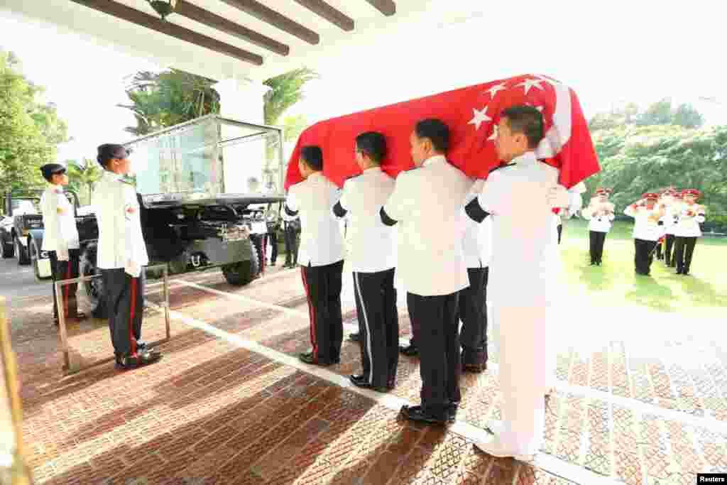 Pasukan Kehormatan membawa peti jenazah perdana menteri pertama Singapura, Lee Kuan Yew, ke atas kereta (25/3).