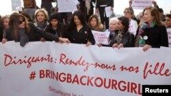 """Mantan Ibu Negara Prancis Carla Bruni-Sarkozy (kiri) dan Valerie Trierweiler (kanan) bersama para politisi dan seniman membawa spanduk yang berbunyi, """"Para Pemimpin, Pulangkan Anak Perempuan Kami"""", dalam demonstrasi di Paris mengutuk penculikan para siswi di Nigeria oleh Militan Boko Haram (13/5/2014)."""