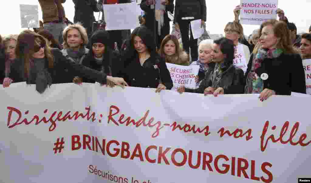 "Former French first ladies Carla Bruni-Sarkozy (left) and Valerie Trierweiler (right) stand with politicians and entertainment artists holding a banner that reads ""Leaders, bring back our girls"" during a demonstration near the Eiffel Tower in Paris, May 13, 2014."