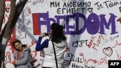 Các bạn trẻ Ai Cập chụp ảnh trước bức tường mới sơn trên một con đường dẫn ra Quảng trường Tahrir ở trung tâm Cairo, Ai Cập, Chủ Nhật 13/2/2011