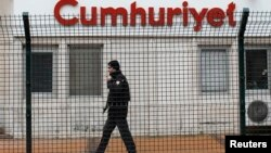 A private security employee stands guard at the entrance of daily newspaper Cumhuriyet's offices, in Istanbul, Jan. 14, 2015.
