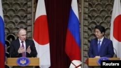 블라디미르 푸틴(왼쪽) 러시아 대통령이 16일 도쿄에서 진행된 공동기자회견에서 발언하는 동안 아베 신조 일본 총리가 듣고 있다.