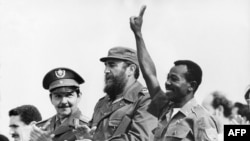 FILE - Ethiopian President Lieutenant Colonel Mengistu Haile Mariam (R) makes V sign as he stands with Fidel Castro (C) and Raul Castro (L) during an official visit in La Havana, Cuba, Apr. 25, 1975. Mengistu took part in the attempted coup against Haile Selassie in 1960 and in 1977 after a further coup he became undisputed ruler of his country. He was overthrown in 1991 by the Ethiopian People's Democratic Front.