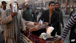 People care for a person injured in a blast in Peshawar, Pakistan, December 3, 2012.