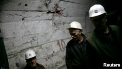 FILE - Miners walk in underground tunnel in Trepca mines, Mitrovica, Nov. 2008.