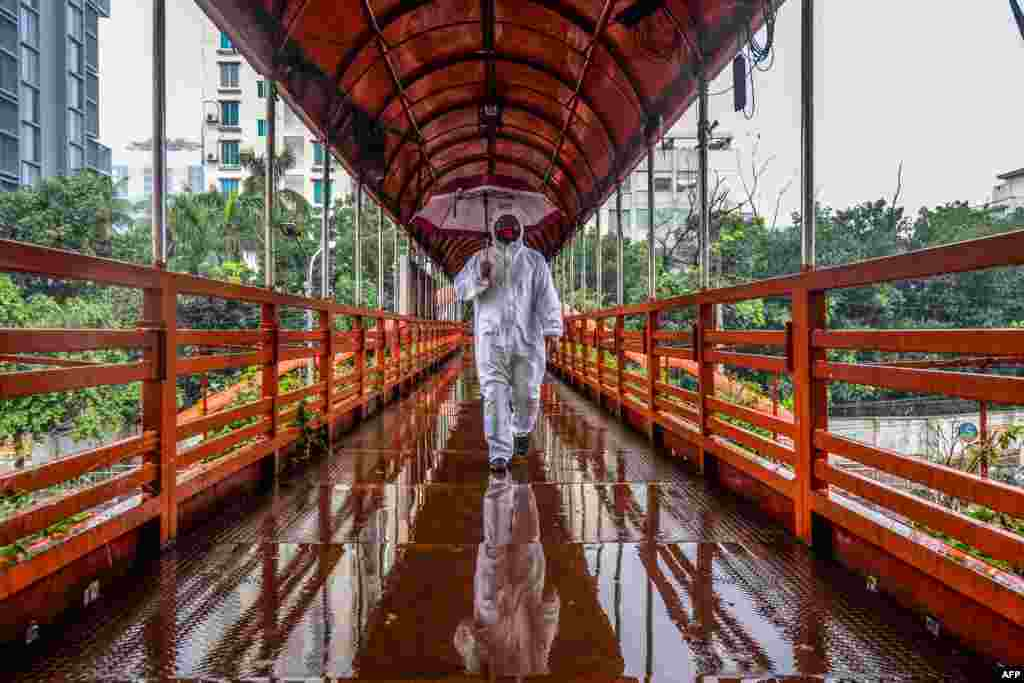 A man wearing protective gear as a preventive measure against the COVID-19 coronavirus walks over a footbridge in Dhaka, Bangladesh.