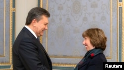 Ukraine's President Viktor Yanukovych (L) shakes hands with European Union foreign policy chief Catherine Ashton during their meeting in Kyiv Dec. 10, 2013.