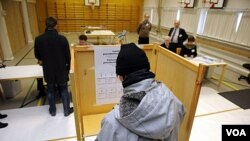 Para pemilih mengisi surat suara mereka di sebuah TPS di Espoo, Finlandia (22/1).