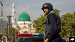 FILE - A Pakistani police officer stands guard outside the Barri Imam shrine, as security is beefed up in the capital following a suicide attack at a Sufi shrine in interior Sindh, Islamabad, Pakistan, Feb. 17, 2017. Pakistan hosted a meeting Wednesday with Russia, China and Iran to discuss counterterrorism cooperation.