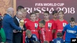 Vladimir Poutine et le président de la Fifa, Gianni Infantino, portent le trophée de la Coupe du monde, Moscou, le 9 septembre 2017.