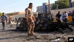 Anggota pasukan keamanan Irak memeriksa lokasi serangan bom mobil di Irbil, Irak.