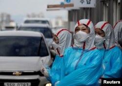 Petugas medis Korea Selatan melakukan tes Covid-19 terhadap para pengendara mobil (foto: ilustrasi).