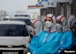 身穿防护服的韩国医护人员在一个检查站对开车通过的人进行新冠病毒感染检测。(2020年3月3日)
