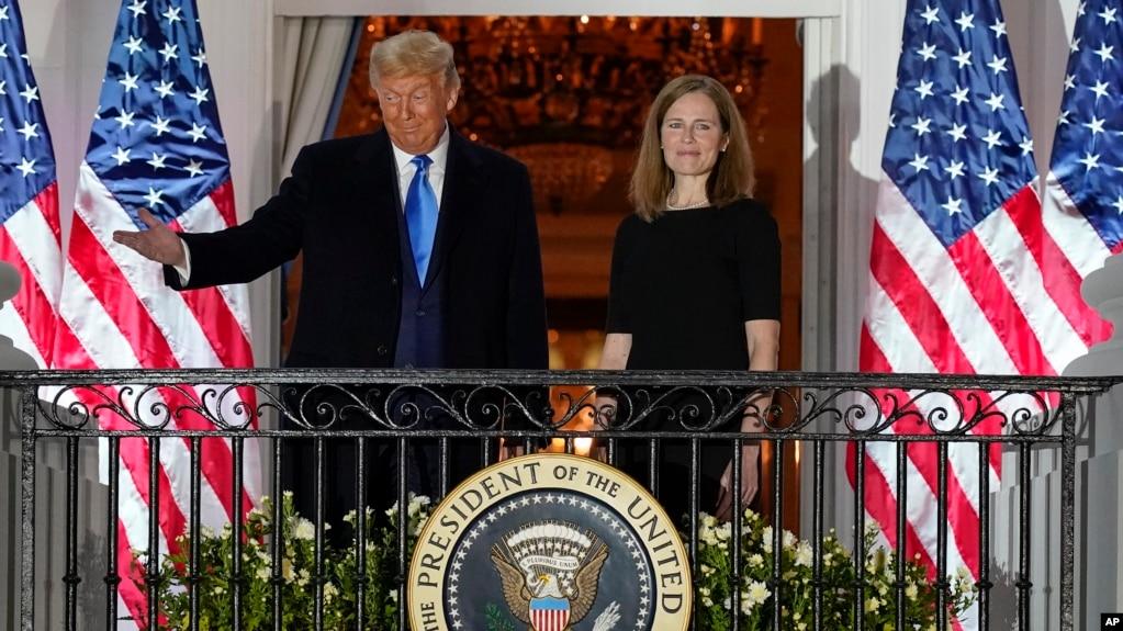 在最高法院大法官托马斯主持宣誓后,特朗普总统与新任最高法院大法官巴雷特站在在白宫蓝屋的阳台上。(2020年10月26日)