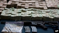 FILE - An assault rifle, and bundles of U.S. dollars and Mexican pesos are displayed in Mexico City, Mexico, June 15, 2012.