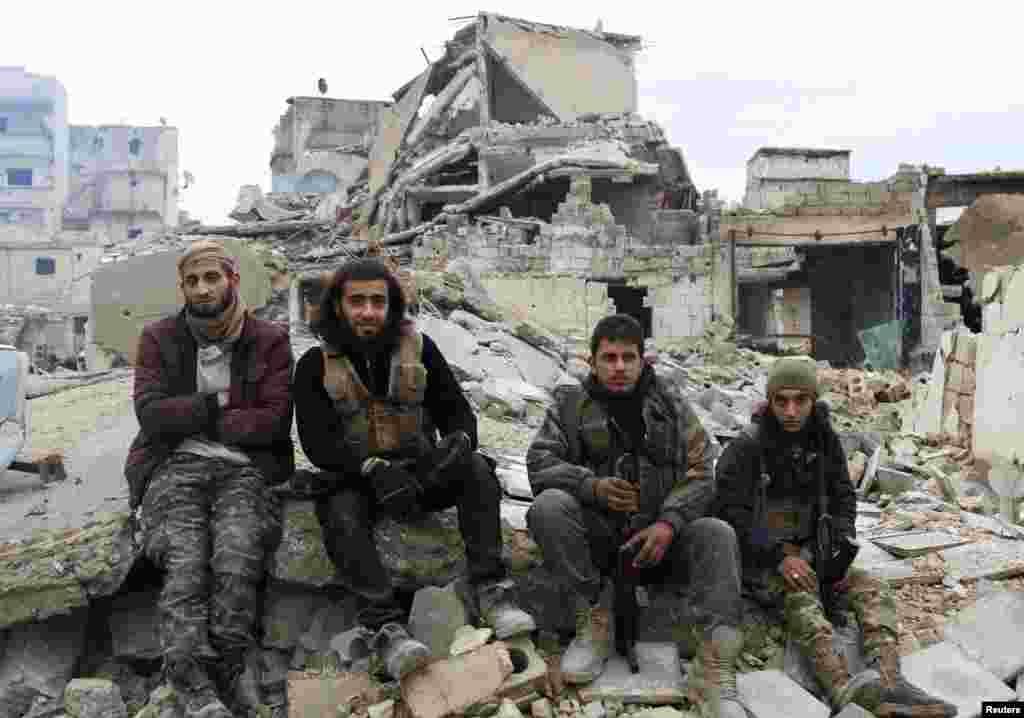شورشیان ضد رژیم بشار الاسد که روی آوار نشسته اند و انتظار می کشند تا از شرق شهر حلب خارج شوند.