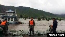 제10호 태풍 '라이언록'이 북중 접경지역에도 피해를 끼쳤다. 지난달 31일 중국 투먼시 일대에서 구급요원들이 두만강 범람을 막기 위해 모래주머니를 쌓고 있다.