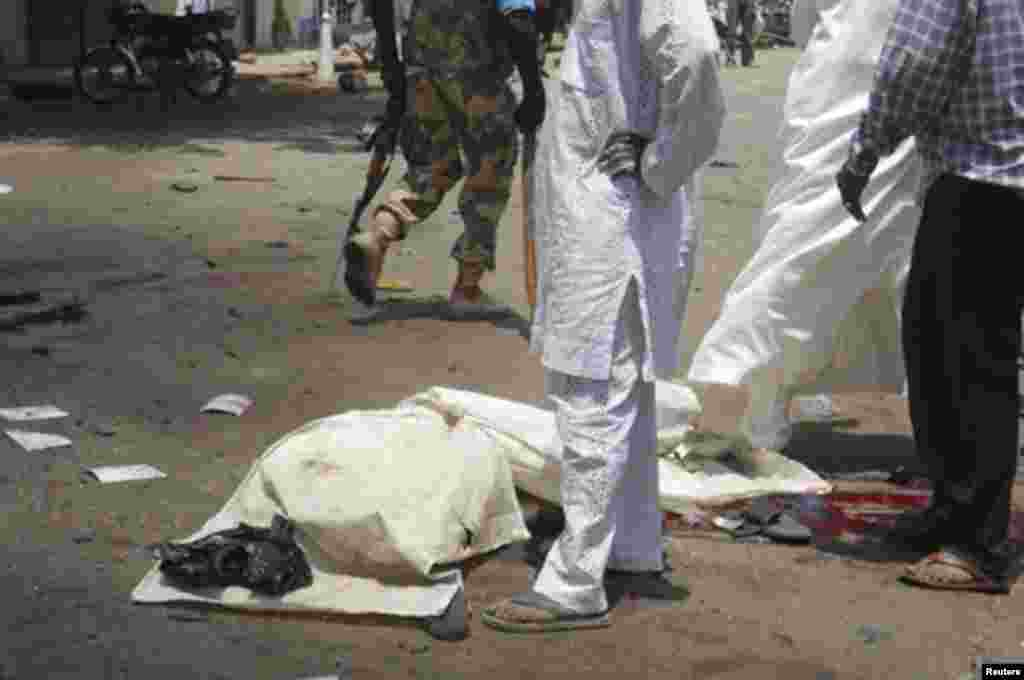 The body of a victim lies covered on the ground after a bomb blast in front of the office compound of Nigerian newspaper This Day in the northern city of Kaduna April 26, 2012.