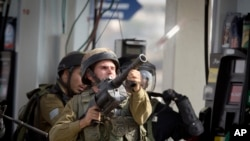 Seorang tentara Israel menembakkan gas airmata dalam bentrokan dengan demonstran Palestina dekat kota Ramallah, Tepi Barat, Senin (12/10)