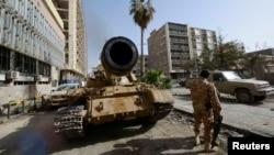 ສະມາຊິກ ທີ່ໜຸນຫຼັງໂດຍກອງກຳລັງລັດຖະບານລີເບຍ ຢືນຢູ່ຂ້າງລົດຖັງ ໃນເມືອງ Benghazi, ລີເບຍ.