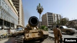 FILE - A member of the Libyan pro-government forces, backed by locals, stands near a tank in Benghazi, Libya, Jan. 21, 2015.