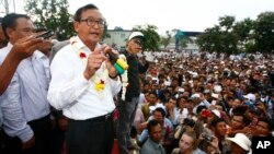 Head of opposition Cambodia National Rescue Party Sam Rainsy, second from left, gives a speech during a rally of their supporters after the July 28 polls, in Phnom Penh, Tuesday, Aug. 6, 2013.