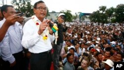 Head of opposition Cambodia National Rescue Party Sam Rainsy, second from left, gives a speech during a rally of their supporters after the July 28 polls, in Phnom Penh, file photo.