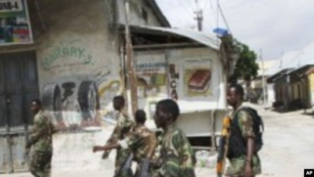 Somali government soldiers patrol in Mogadishu's Bakara market, August 8, 2011