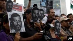 Manifestantes portan fotos de Ruben Espinosa, periodista asesinado en México durante una protesta el domingo, 2 de agosto de 2015.